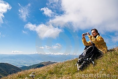 Young woman in mountains - taking picture