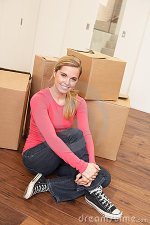 Young woman on moving day sitting on floor
