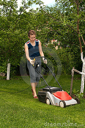 Young woman mow grass