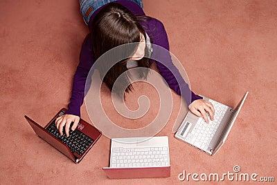 Young woman multitasking three laptop lying
