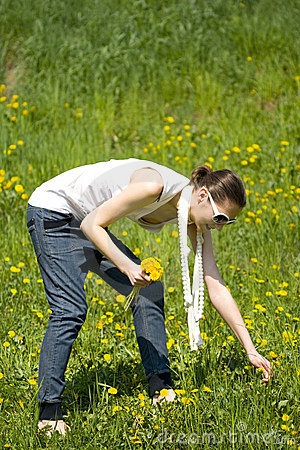 Young woman in nature picking flowers