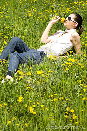 Young woman in nature smelling a flower
