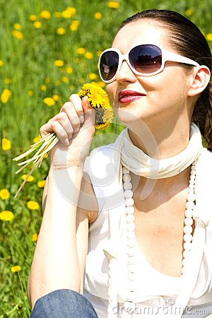 Young woman in nature smelling flowers