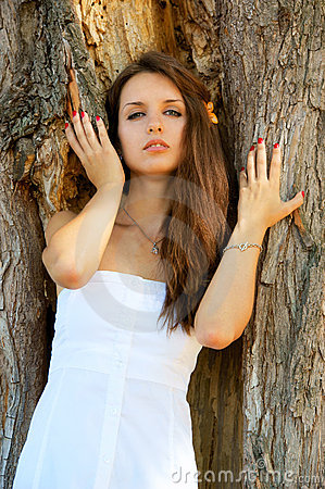Young woman near big tree