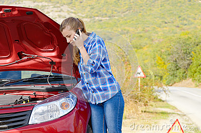 Young woman near broken car speaking by phone