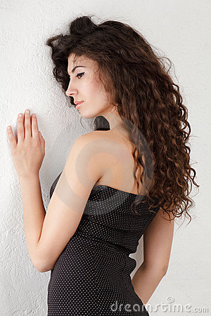 Young woman near wall