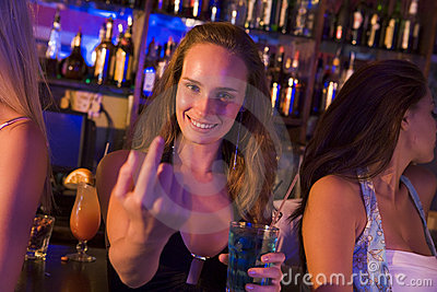 Young woman in nightclub beckoning to camera