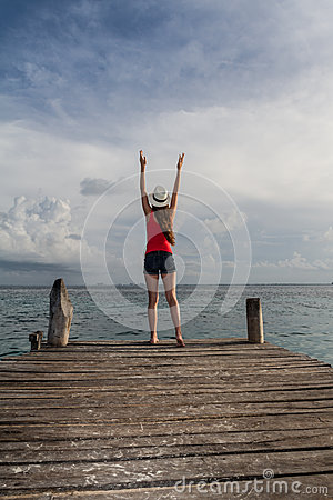 Young woman with open arms enjoying the sunset at the sea