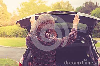 Young woman opening trunk of car