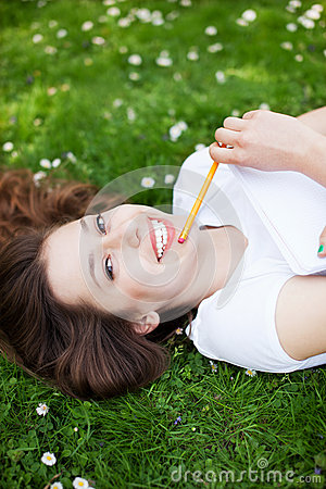Young woman outdoors with workbook and pencil