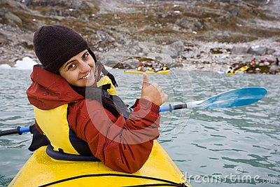 Young woman paddling in yellow kayak