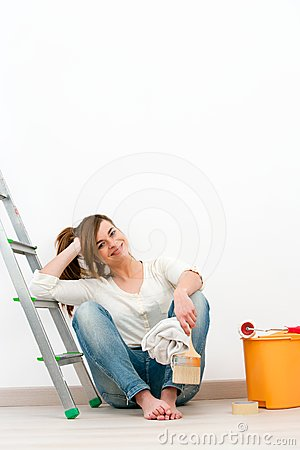 Young woman painter sitting on floor.