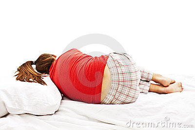 Young woman in pajamas laying in bed