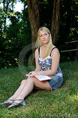 Young woman in park writing in journal or diary