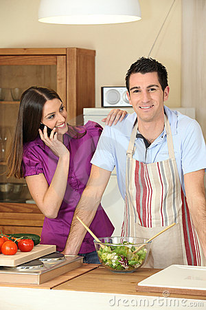 Young woman on phone and young man in kitchen