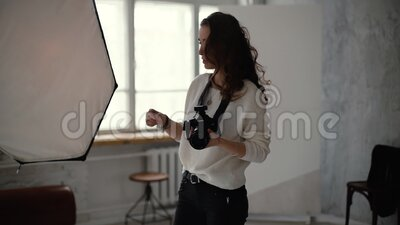 Young woman photographer with professional camera gives instructions to model. In light photo studio, on background of softbox. Concept of creative work in stock footage