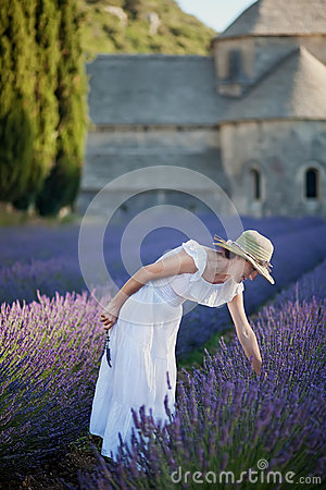 Free Young Woman Picking Some Lavender Close To The Medieval Abbey Of Stock Photo - 39038310
