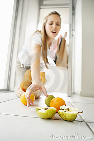 Young woman picking up fruits from floor at home