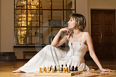 Young  woman play chess in the rich interior