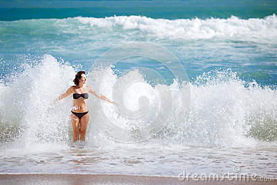 Young woman playing in big waves