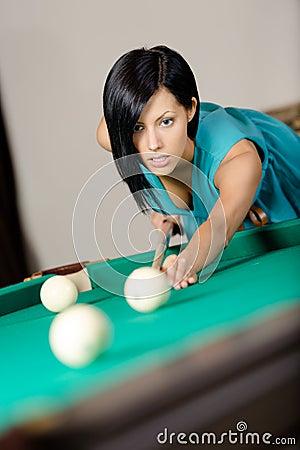Young woman playing billiard