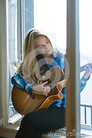 Free Young Woman Playing Guitar On Window Stock Image - 39154921