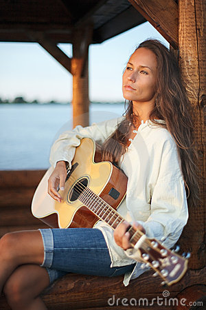 Young woman playing guitar outdoor on sunset