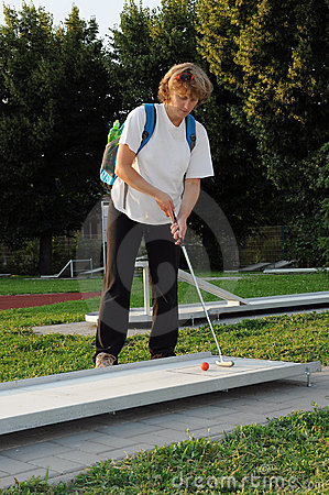 Young woman playing mini golf