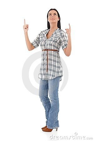 Young woman pointing and looking up smiling Stock Photo