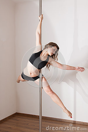 Young woman pole dancing
