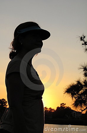 Young woman by pond at sunset