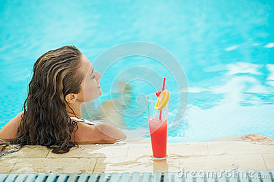 Young woman at pool with cocktail. rear view