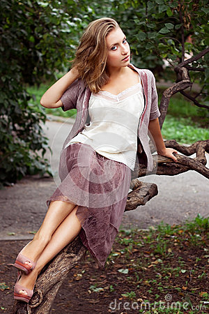 Young woman poses on tree branch