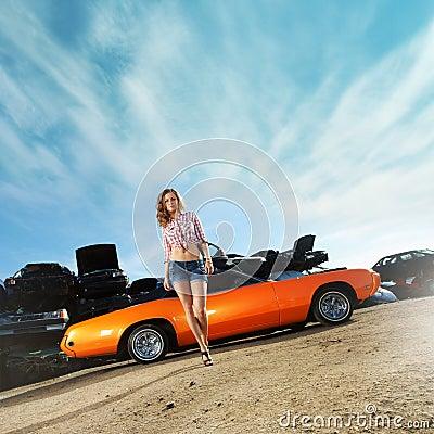 A young woman posing near an orange muscle car