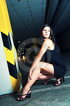 Young woman posing in underground garage