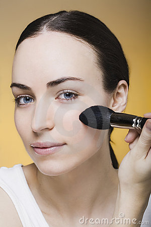 Young woman powders her skin with a makeup brush