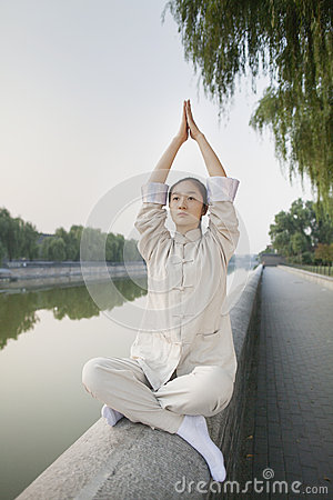 Young Woman Practicing Tai Ji, Arms Raised, by the Canal