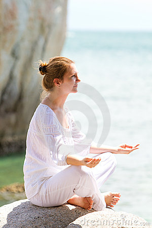 Young woman practicing yoga by coast
