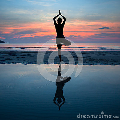 Young woman practicing yoga at sunset on the coast