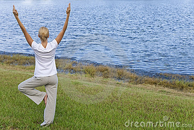 Young Woman Practicing Yoga By Tranquil Blue Lake