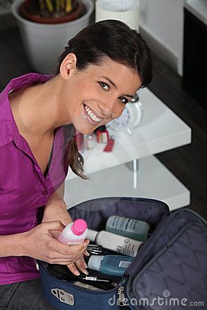 Young woman preparing beauty case