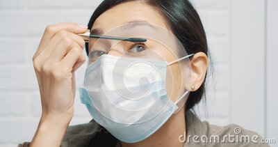 young woman in protective surgical mask doing eye makeup