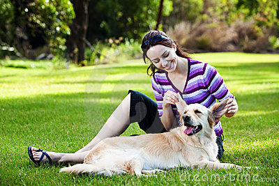 Young woman pulling ears of golden retriever