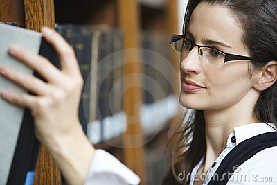 Young woman pulling out book