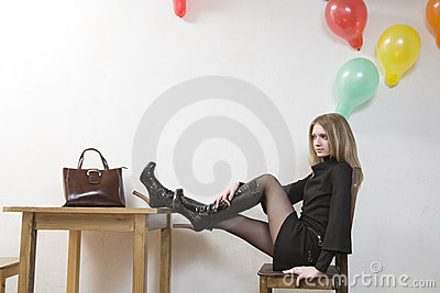 Young woman puts her legs on table