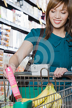 Free Young Woman Putting A Packet In A Shopping Trolley Stock Image - 36095571