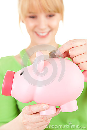 Young woman putting euro coin in piggy bank