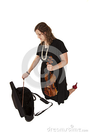 Young woman putting her violin away in her case