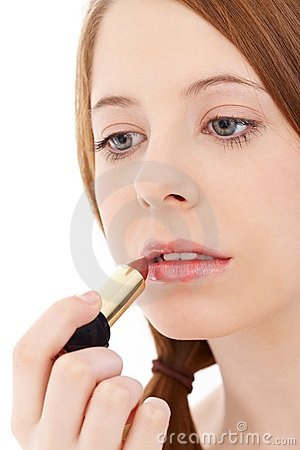 Young woman putting lipstick on