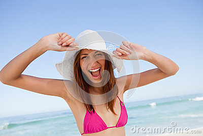 Young woman raising her arms in happiness in front of the sea
